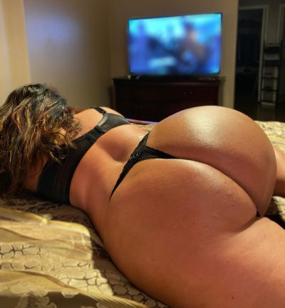 Sexy wife flaunts her juicy ass in a black thong while watching tv. Amateur MILF is lying on the bed to show her juicy booty in tight thongs