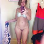 Blonde MILF takes self shot while getting undressed. Sexy woman without panties takes a nude selfie in the changing room