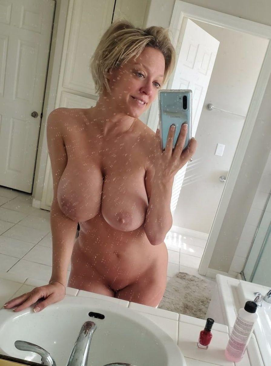 Big Tits MILF takes naked bathroom selfie of her huge breasts. Busty amateur wife bres her huge boobs and shaved pussy for mirror self shot