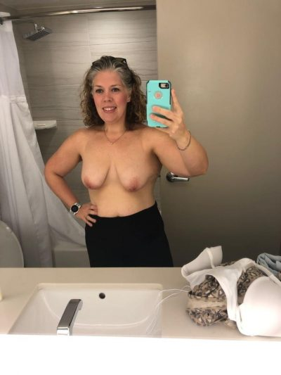 Mature woman takes selfie of her natural tits in bathroom mirror. Charming old wife with nice natural tits stripping home alone