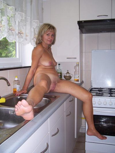 Amateur MILF removes lingerie for totally nude poses in the kitchen. Hot wife spreads legs her naked pussy in the kitchen