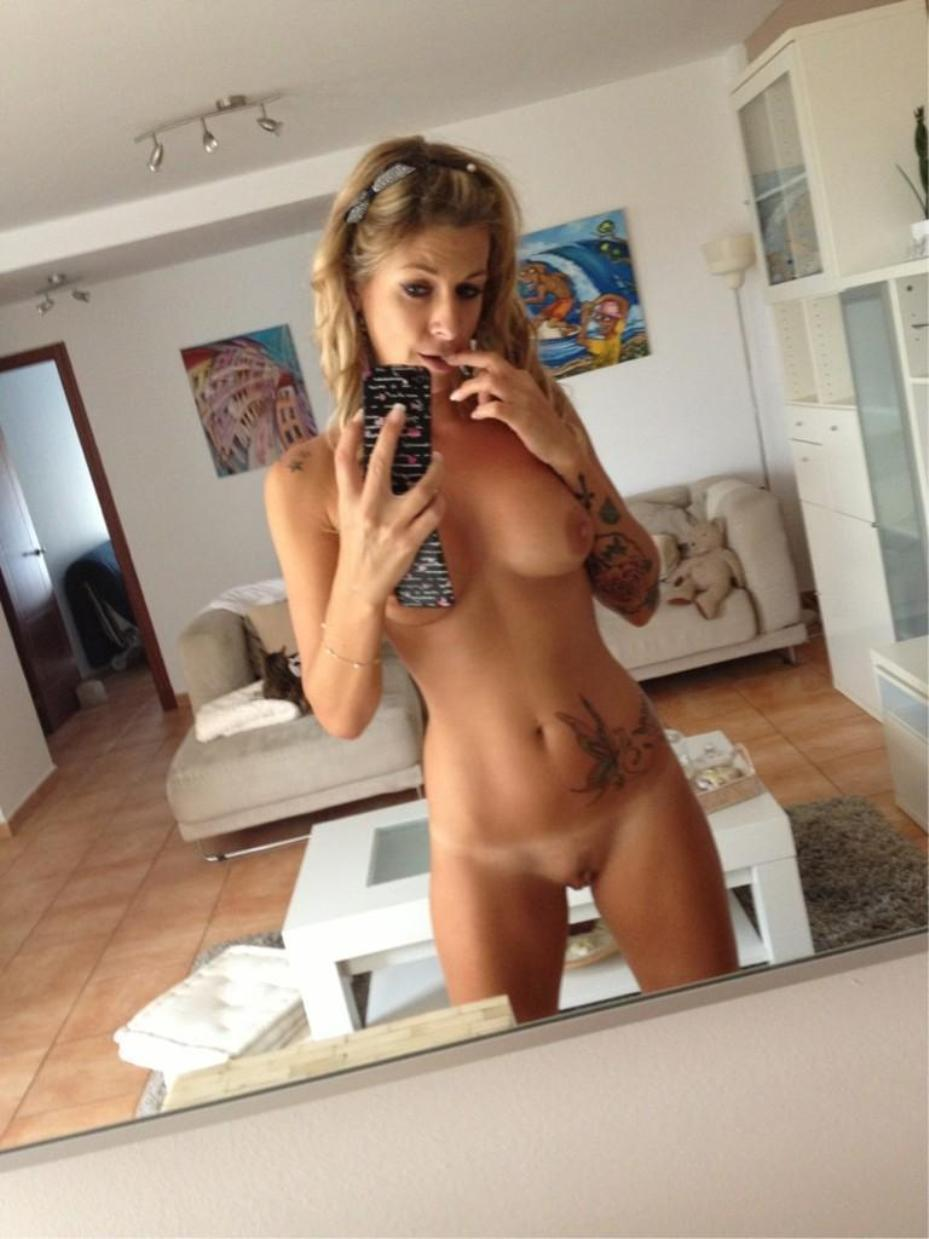 Gorgeous cougar takes closeup selfie of her perfect body. Sexy MILF takes nude self shot while exposing herself in mirror