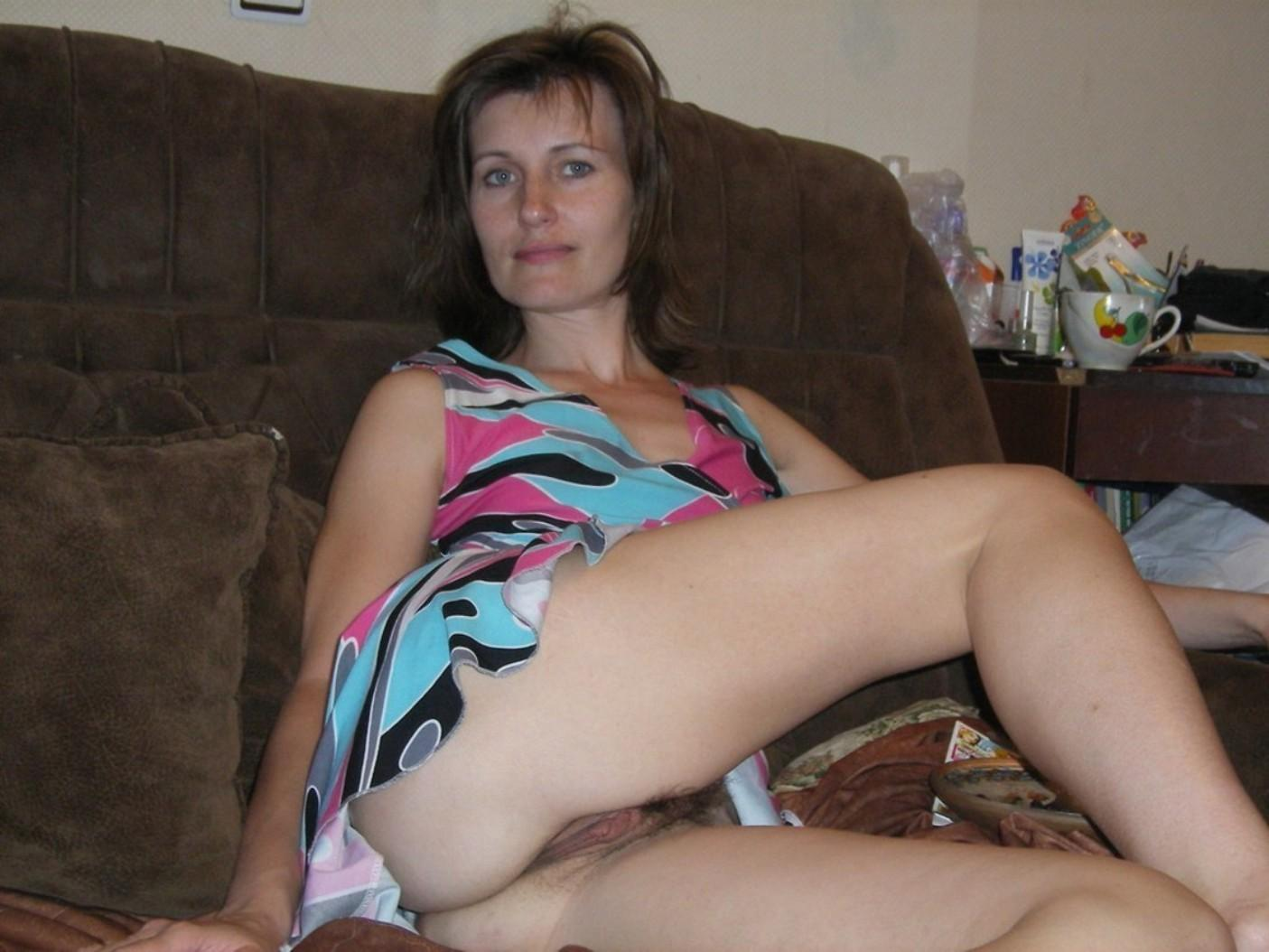 Beautiful wife delights in showing off her bush twat. Russian MILF stripping down naked on the couch and showing hairy pussy