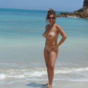 Busty MILF posing naked on a sandy beach