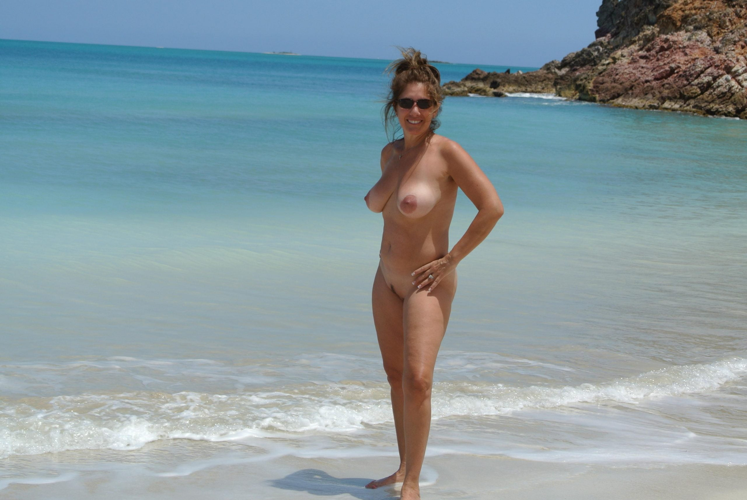 Busty MILF displays her great body while totally naked by the sea. Pretty wife demonstrates nice tits and pussy on the beach