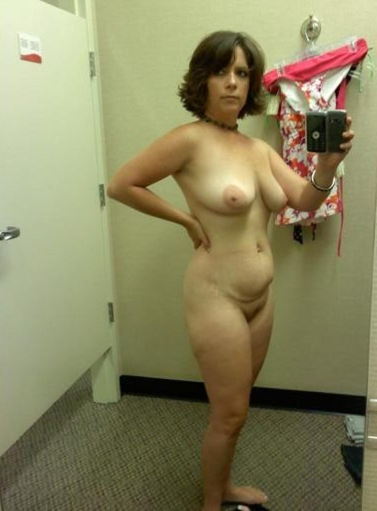 Brunette Mom loves taking selfie of attractive nude body in dressing room. Amateur wife takes mirror selfie while removing dress
