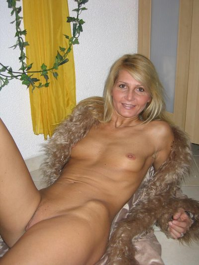 Beautiful naked MILF displays her small boobs while stripping in the living room. Ripe wife lets you see her perfect body when she is lying on the floor