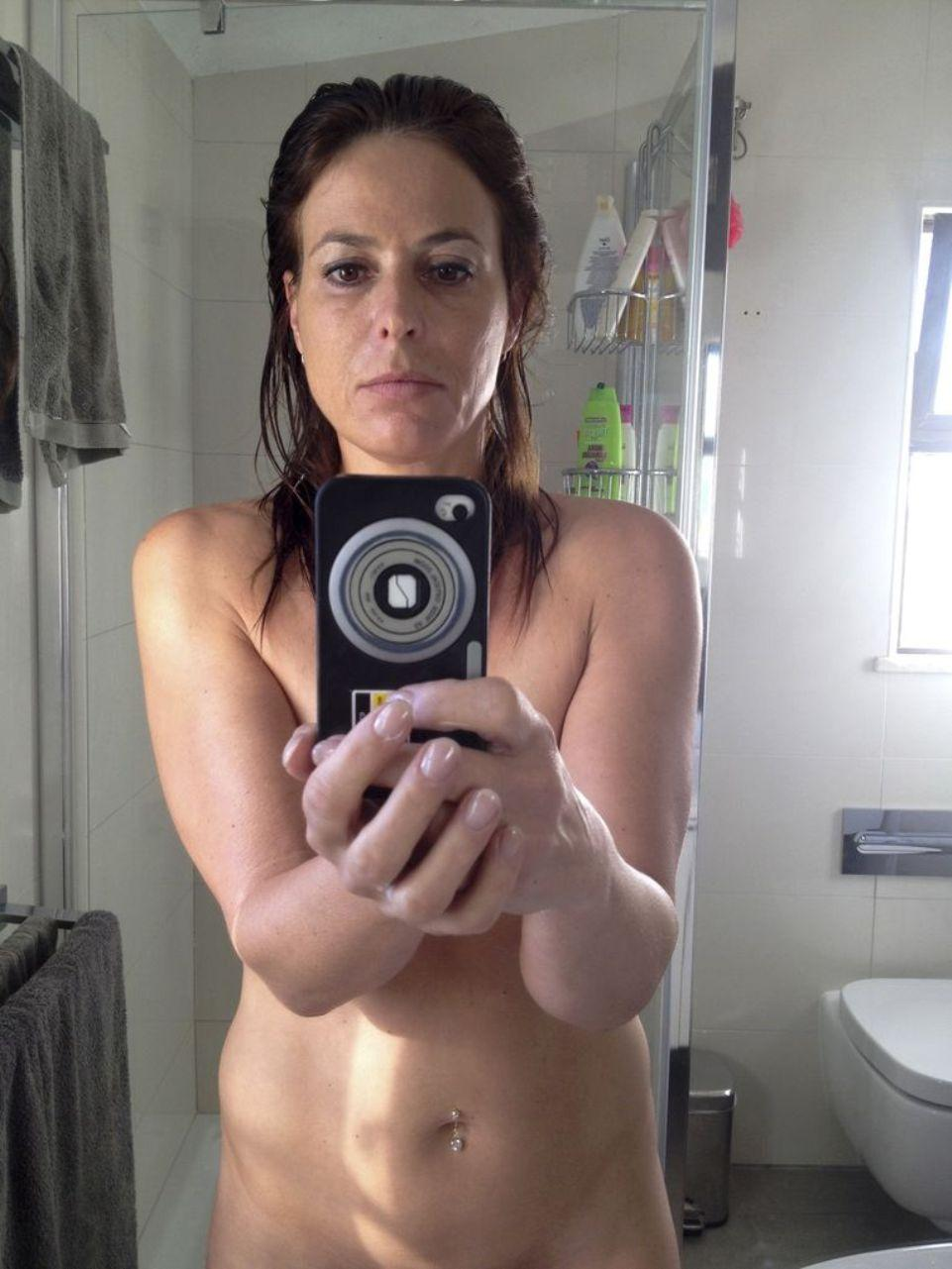 Brunette mature takes mirror selfies while stripping naked in bathroom. Naked wife make selfie of her natural body in bathroom mirror