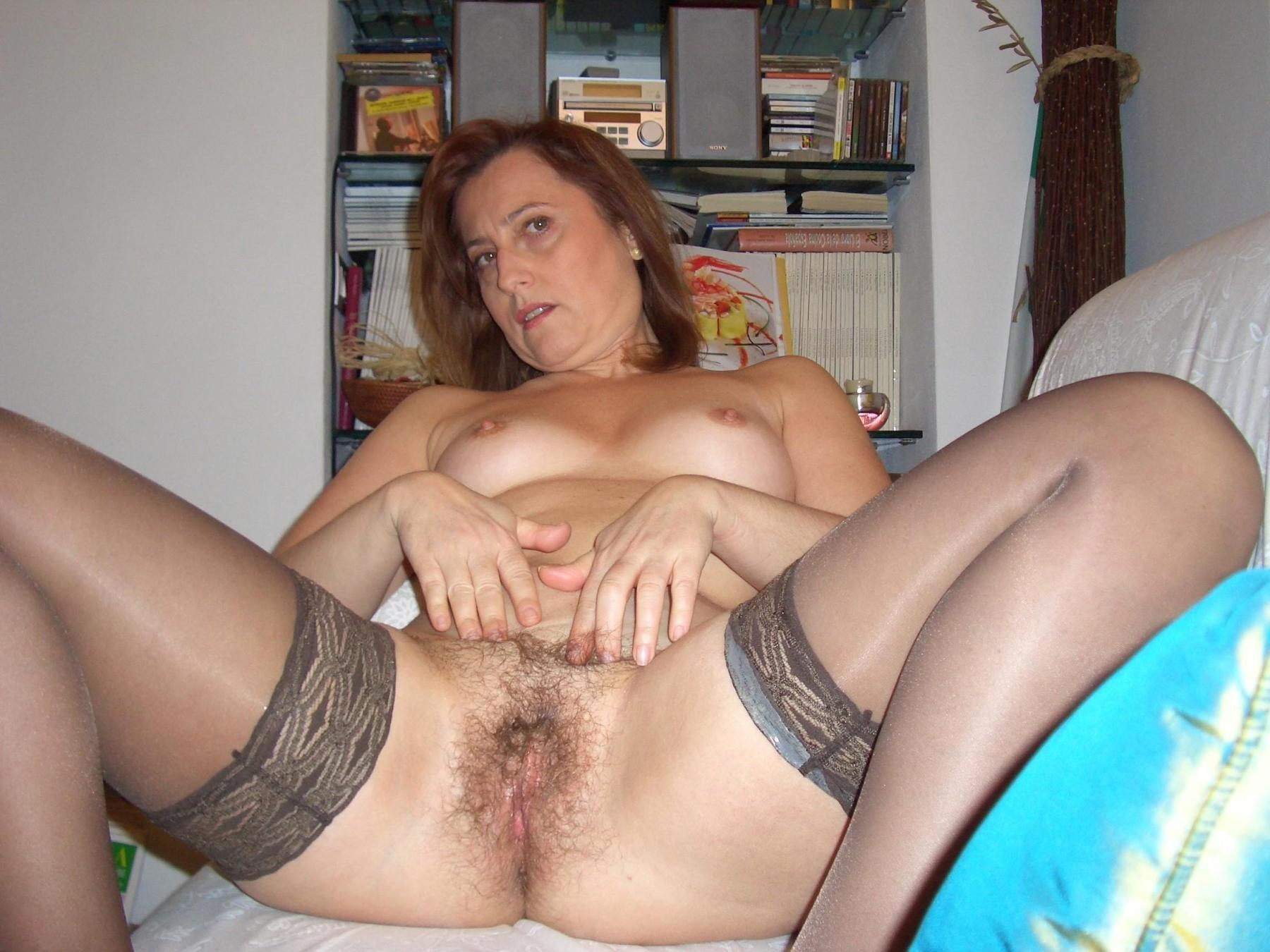 Sexy mature wife stretches out her hairy cunt on a sofa. Nude amateur old lady spreads her pussy wide open in stockings