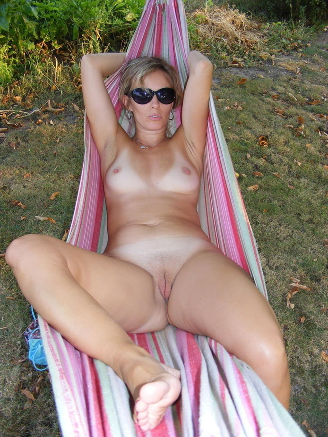 Milf Cougar spreads her bare legs on a hammock outdoor. Sexy mature blonde with sunglasses sunbathing naked on the hammock