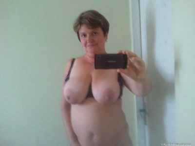 Naked fat wife takes a closeup self shot of her nice natural boobs. Brunette amateur mature exposes her saggy tits in mirror for selfie