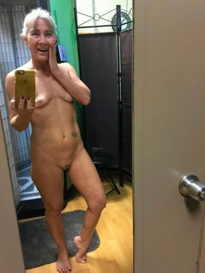 Sexy grannie completely naked presents a hot body in front of the mirror. Granny with white hair exposed takes nude selfie at home