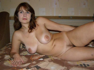 Russian mature with natural tits and hairy pussy posing nude. Busty housewife from Russia flashes hairy pussy lying on the couch in bedroom