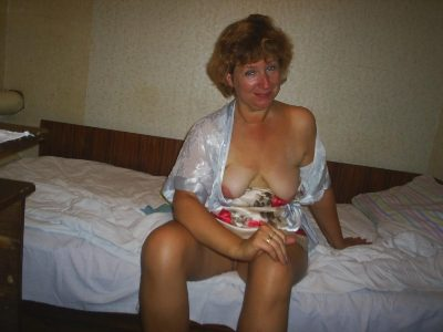Russian wife charms us with nice naked tits. Hot mature from Russia sits with her nude breasts on her bed in morning