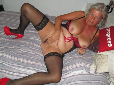 Horny granny reveals her nice big natural tits and bald pussy. Old lady naked fingering her hungry pussy lying on the bed