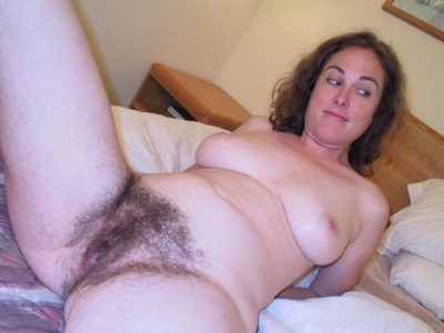 Amateur MILF showing her natural boobs & bush cunt up close. Nude wife expose her hairy pussy after undressing on a bed