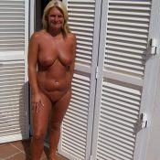 Naked elderly woman is tanning her natural body