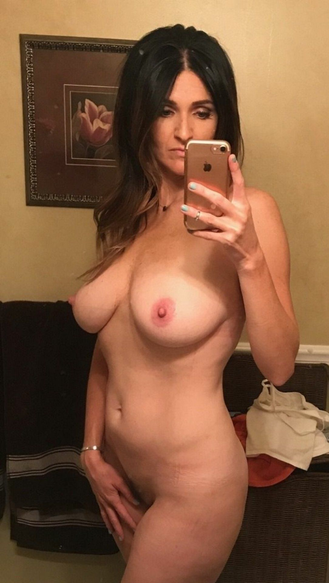 Sexy cougar undressing in front of the mirror and making naked selfie. Perfect MILF removes her bra and panties for nude self shot