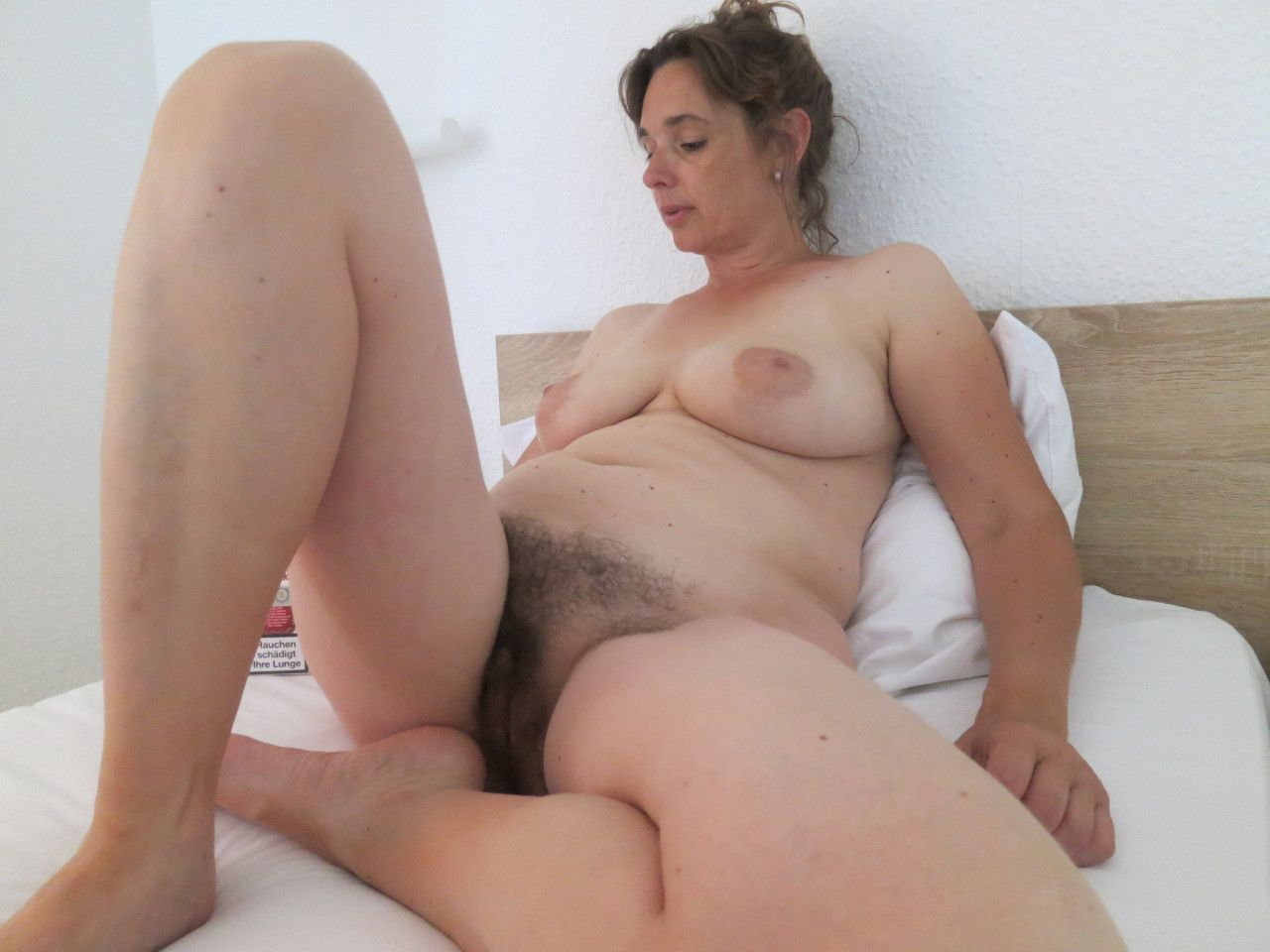 Sweet old lady with hairy cunt posing on the bed. Mature babe nude shows off her hairy cunt and natural tits lying on the bed