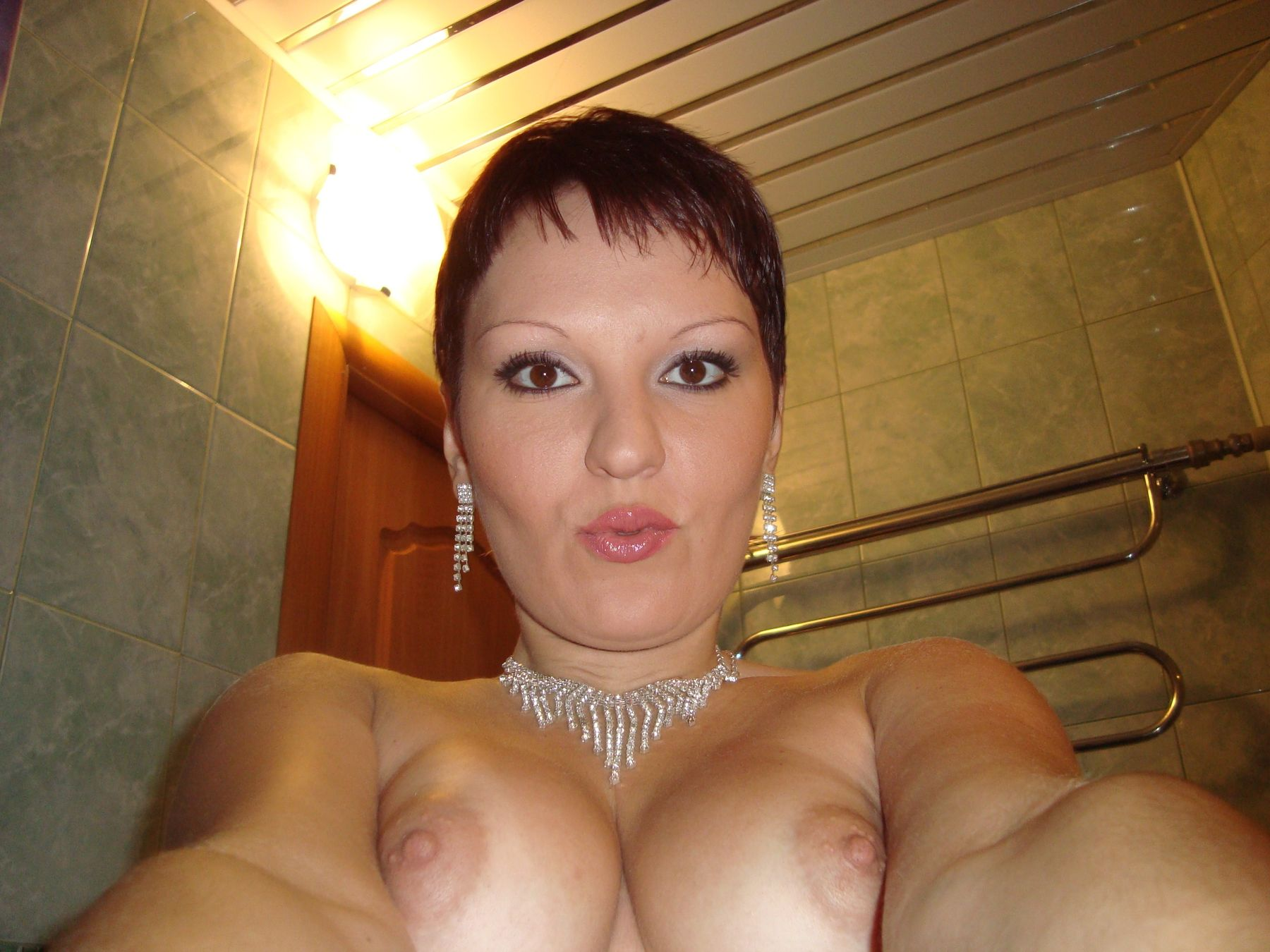 Hot amateur mature removes her bra for nude self shot. MILF whips out her big natural tits for selfie picture