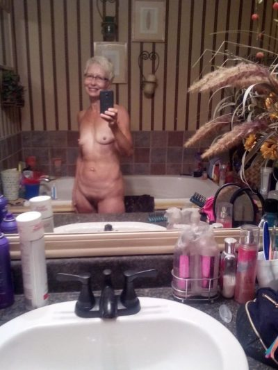 Hot granny strips and gets naked for nude self shot. Old lady with tiny tits undressing and picturing herself in the bathroom