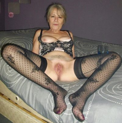Sexy mature showcases her smooth pussy while naked on her bed. Beautiful old lady spreading her legs in a stockings