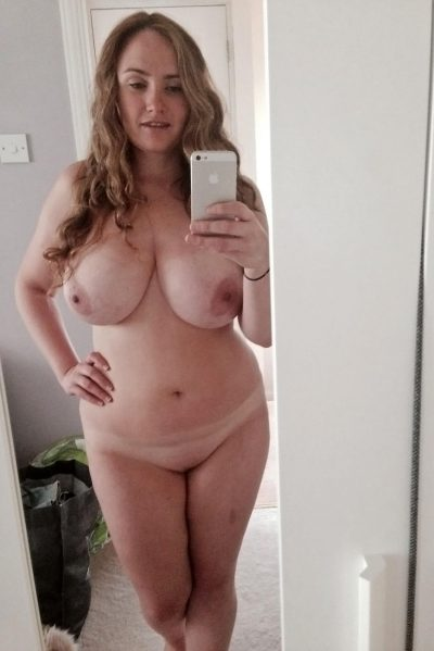 Busty amateur MILF taking photos of her amazing boobs. Mature nude woman standing in front of the mirror takes hot nudes