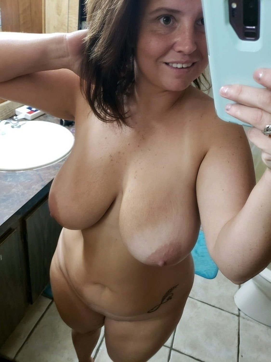 Attractive mature takes selfie while showing nice tits and sexy body. Brunette amateur wife uncovering her huge boobs for nude selfshot
