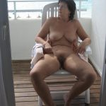 Nude mature brunette tans natural tits and hairy cunt. Beautiful naked wife resting on the balcon lying deck chair