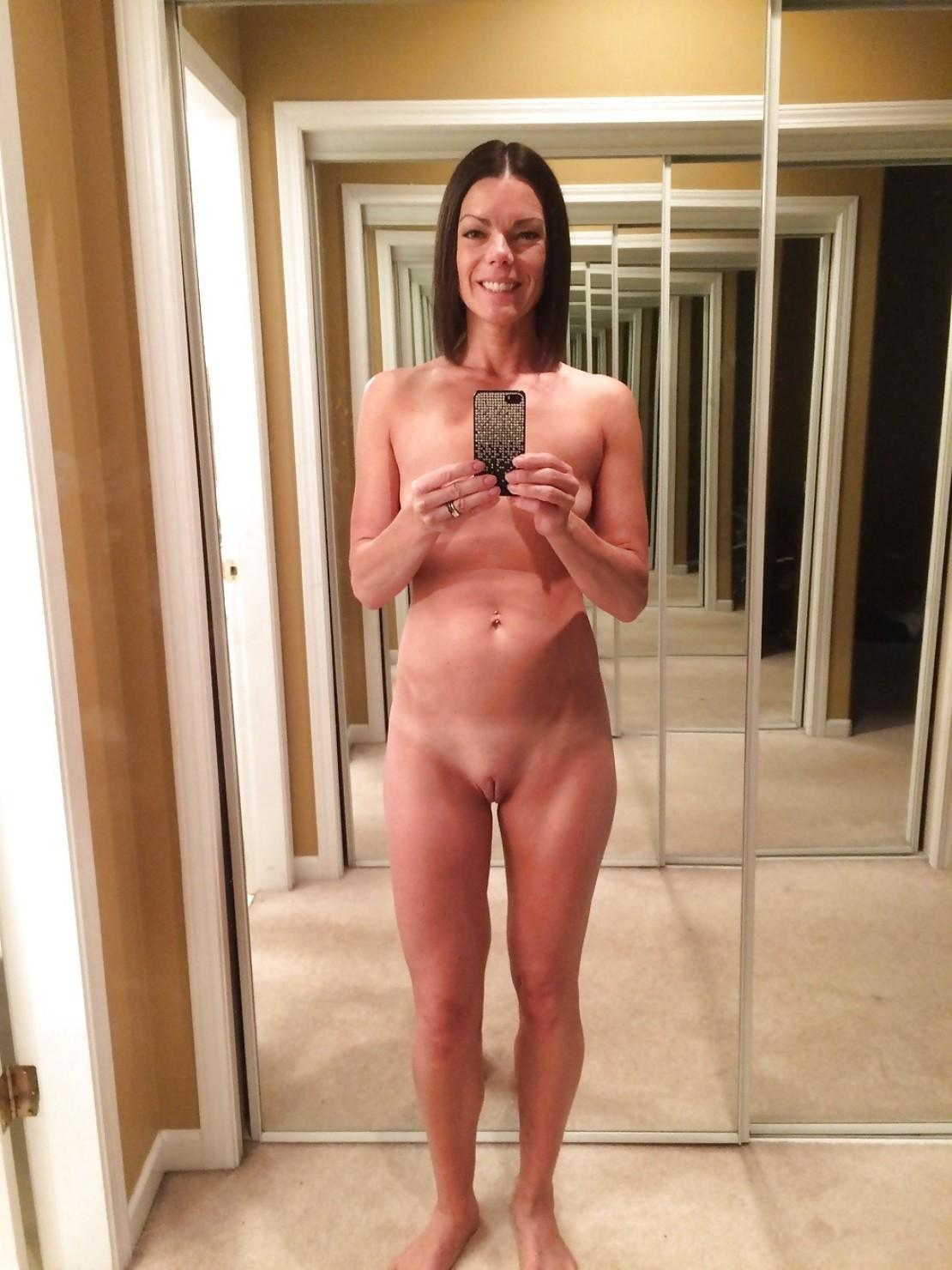 Cute slim mom takes self shots in a mirror while getting naked. Hot amateur wife take self shots of her small tits and bald pussy