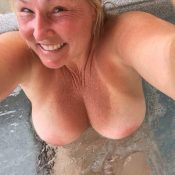 Beautiful mom takes a selfie while relaxing in jacuzzi