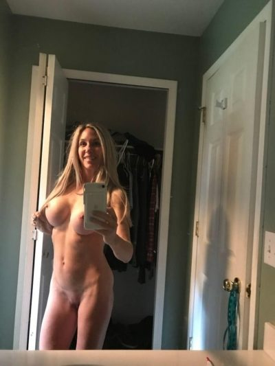 Nude busty MILF shows off her big breasts and shaved cunt. Sexy naked wife with huge tits is doing nudes in front of the mirror