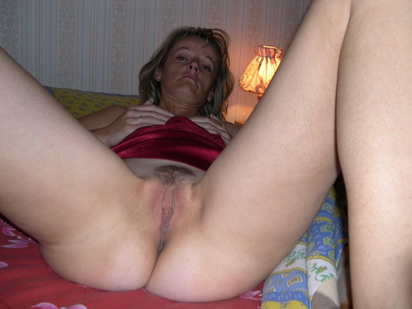 Skinny wife lying on the bed reveals her abundant hairy hot vagina. Nude amateur mom exposing her furry pussy on a erotic pic
