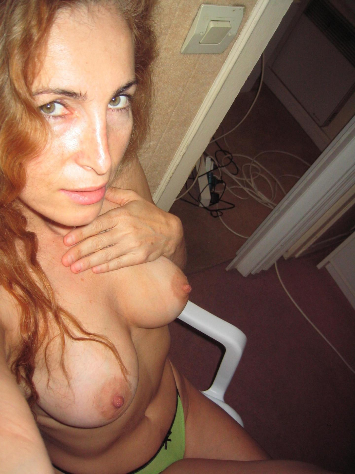 Hot milf topless shows off beautiful breasts. Sexy mom with big tits snaps erotic nudes while sitting on a chair
