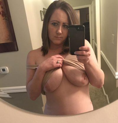 Young MILF pulls t-shirt up to show off her natural tits. Busty amateur wife making a tits selfie and getting naked