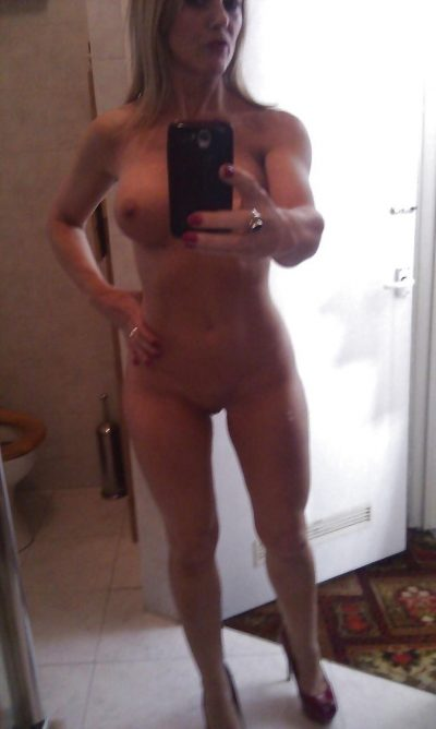 Big titted wife strips and poses in high heels. Mysterious MILF with big breasts and a bald pussy takes a nude selfie in the bathroom