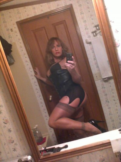 Milf in lingerie tempts with erotic curves in front of the mirror. Kinky mom take hot selfie of her sexy body in the mirror